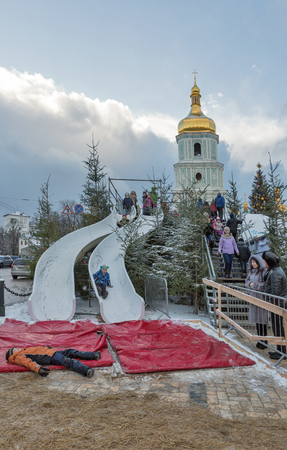 KIEV, UKRAINE - JANUARY 03, 2017: Kids have fun on Christmas fair slides in front of Saint Sophia Cathedral bell tower. Saint Sophia Cathedral is an outstanding architectural monument of Kievan Rus. Editorial