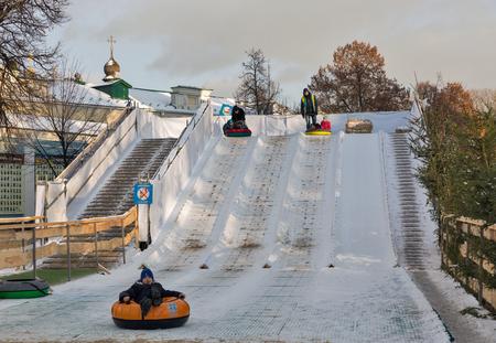 KIEV, UKRAINE - JANUARY 03, 2017: Kids have fun on Christmas fair snow slides in front of Saint Sophia Cathedral bell tower. Saint Sophia Cathedral is an outstanding architectural monument of Kievan Rus.