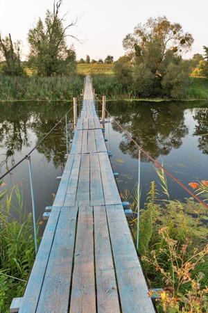 Suspended wooden footbridge over the River Ros, Central Ukraine.
