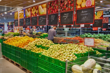 KIEV, UKRAINE - AUGUST 20, 2015: Unrecognized buyers choose fruits and vegetables in Fozzy hypermarket. Fozzy Group is Ukraines largest supermarket company and food retail group.