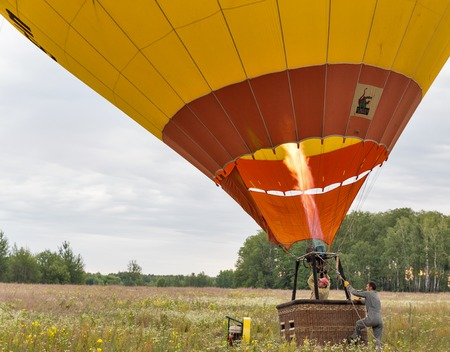 MAKARIV, UKRAINE - JULY 01, 2017: Unrecognized workman controls hot air balloon preparing to flight. Hot air from a gas burner fills the dome of the balloon.