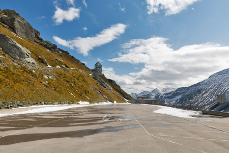 Mountain side with Wilhelm Observation Tower and empty parking lot on Kaiser Franz Josef glacier. Grossglockner High Alpine Road in Austrian Alps.