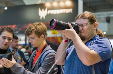 EXHIBIDOR: KIEV, UKRAINE - OCTOBER 07, 2017: Unrecognized visitors testing professional photographic cameras on Nikon booth during CEE 2017, the largest electronics trade show of Ukraine in KyivExpoPlaza EC.