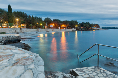 Mediterranean sumer resort with Adriatic sea rocky beach at evening. Istria, Croatia