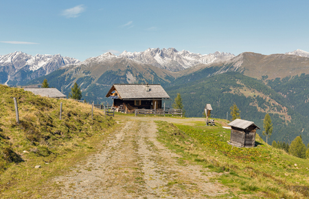 Wooden shepherd lodge on a highland pasture with Alpine mountain landscape in Western Carinthia, Austria.