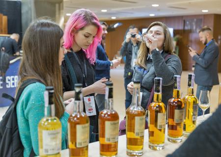 KIEV, UKRAINE - NOVEMBER 25, 2017: Unrecognized young woman tasting Single Malt Scotch Whisky at 3rd Ukrainian Whisky Dram Festival in Parkovy Exhibition Center.