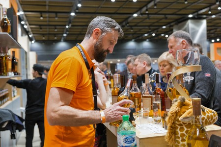 KIEV, UKRAINE - NOVEMBER 25, 2017: Unrecognized presenter works on Glenmorangie Single Malt Scotch Whisky Highland distillery booth at 3rd Ukrainian Whisky Dram Festival in Parkovy Exhibition Center. Editorial