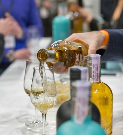 KIEV, UKRAINE - NOVEMBER 25, 2017: Unrecognized sommelier pours Single Malt Scotch Whisky into glass at 3rd Ukrainian Whisky Dram Festival in Parkovy Exhibition Center. Editorial
