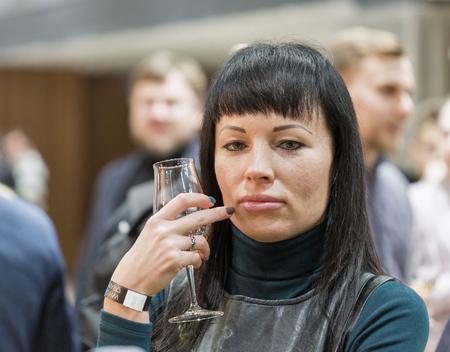 KIEV, UKRAINE - NOVEMBER 25, 2017: Unrecognized white middle aged woman tasting Single Malt Scotch Whisky at 3rd Ukrainian Whisky Dram Festival in Parkovy Exhibition Center.