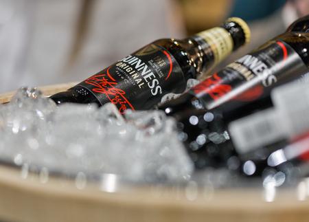 KIEV, UKRAINE - NOVEMBER 25, 2017: Guiness beer bottles closeup in a wooden bucket at 3rd Ukrainian Whisky Dram Festival in Parkovy Exhibition Center. Editorial