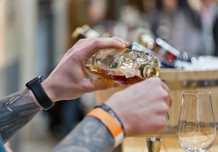 KIEV, UKRAINE - NOVEMBER 25, 2017: Unrecognized sommelier pours Single Malt Scotch Whisky into measuring cup at 3rd Ukrainian Whisky Dram Festival in Parkovy Exhibition Center. Editorial
