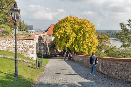 BRATISLAVA, SLOVAKIA - SEPTEMBER 25, 2017: People walk along medieval castle alley, gate and wall. It is one of the most prominent structures in the city, situated 85 m above the Danube river.