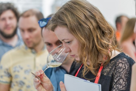 KIEV, UKRAINE - JUNE 2, 2018: Young woman tastes white wine at Kyiv Wine Festival. Big festival of wine and food was organized by Good Wine company, 77 winemakers from around the world took part there. Editorial
