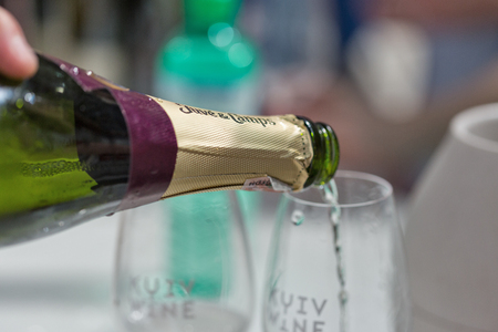 KIEV, UKRAINE - JUNE 02, 2018: Pouring white sparkling wine closeup at Kyiv Wine Festival. 77 winemakers from around the world took part in the big festival organized by Good Wine company.
