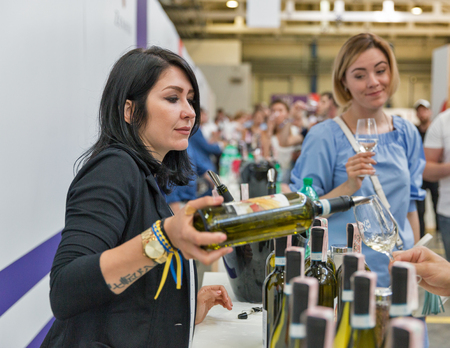 KIEV, UKRAINE - JUNE 02, 2018: Woman sommelier pours white wine at Kyiv Wine Festival booth. 77 winemakers from around the world took part big festival organized by Good Wine company. Editorial