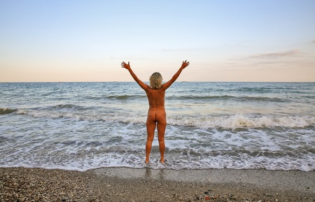 Beautiful naked woman stands with her back in the sand on the sunset sea beach 版權商用圖片