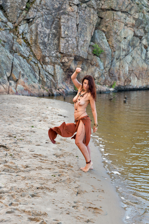 young caucasian beautiful naked Amazon woman on the sand river beach in front of rocks