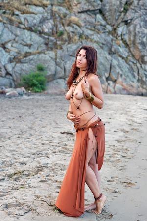 giovane indoeuropea bella donna Amazon sulla spiaggia del fiume di sabbia di fronte a rocce