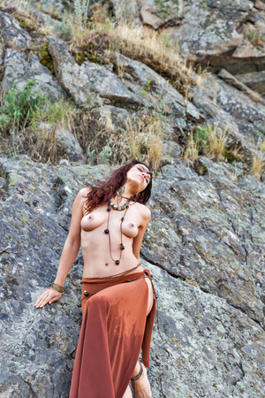young caucasian beautiful naked Amazon woman stands in front of rocks. 免版税图像