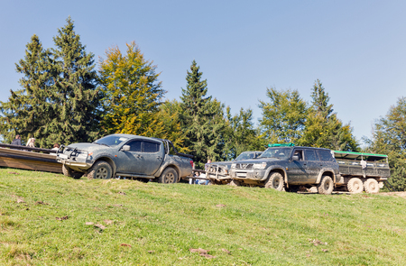MIKULICZYN, UKRAINE - SEPTEMBER 14, 2018: Tourists take part in adventure extreme tour on quads, SUVs and truck to Carpathian Mountains. It is the second longest mountain range in Europe. Standard-Bild - 113516648