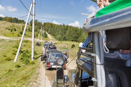 MIKULICZYN, UKRAINE - SEPTEMBER 14, 2018: Tourists take part in adventure extreme tour on quads, SUVs and truck to Carpathian Mountains. It is the second longest mountain range in Europe.
