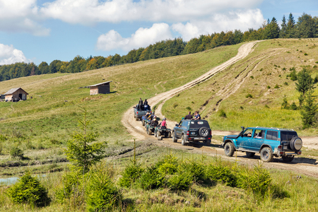 MIKULICZYN, UKRAINE - SEPTEMBER 14, 2018: Tourists take part in adventure extreme tour on quads and SUVs to Carpathian Mountains. It is the second longest mountain range in Europe.
