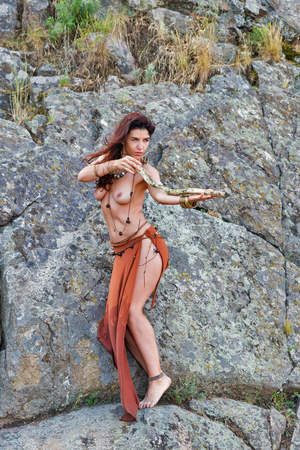 young caucasian beautiful naked Amazon woman stands with wooden stick in front of rocks.