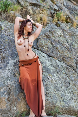 young caucasian beautiful naked Amazon woman stands in front of rocks