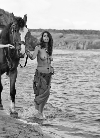young caucasian beautiful naked Amazon woman on the river shore with red horse. black and white.