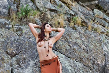 junge kaukasische schöne Amazonasfrau steht vor Felsen