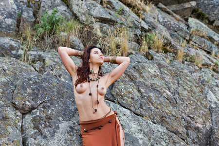 young caucasian beautiful naked Amazon woman stands in front of rocks 版權商用圖片 - 109155053