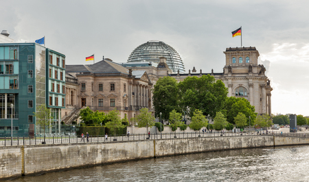 BERLIN, GERMANY - JULY 13, 2018: Cityscape of the Mitte district with Spree river, Reichstag or Bundestag and German Parliamentary Society buildings. Berlin is the capital and largest city of Germany.