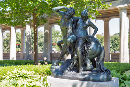 BERLIN, GERMANY - JULY 14 , 2018: Centaur and Nymph statue in public garden of the Old Museum at Museum Island in front of The Old National Gallery.