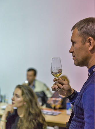KIEV, UKRAINE - OCTOBER 20, 2018: Unrecognized people taste whisky at 4th Ukrainian Whisky Dram Festival organized by Good Wine company in Artistic Arsenal.
