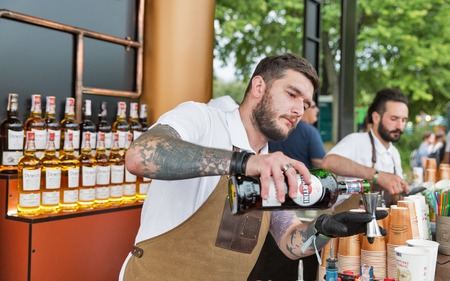 KIEV, UKRAINE - JULY 04, 2018: Young man bartender works in Bacardi outdoor bar at the Atlas Weekend Festival in National Expocenter. Bacardi is the largest family owned spirits company in the world. Publikacyjne