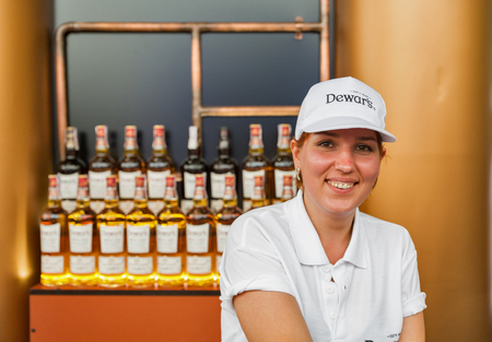 KIEV, UKRAINE - JULY 04, 2018: Dewar's blended Scotch whisky young woman bartender works in bar at the Atlas Weekend Festival in National Expocenter. It is world most awarded blended Scotch whisky. Editöryel