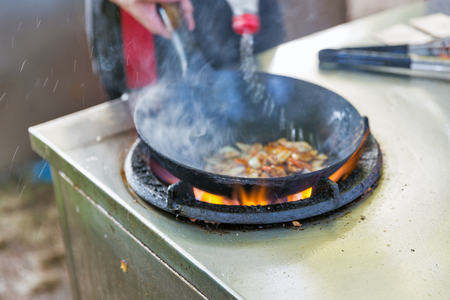 outdoor cooking asian food in a wok on the gas stove closeup 免版税图像