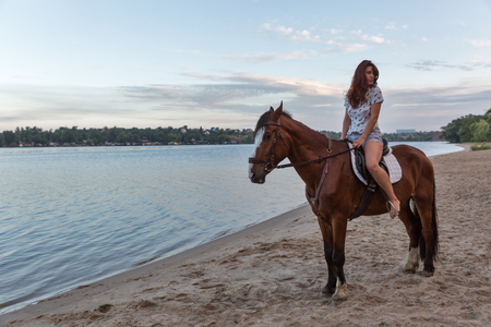 landscape with young caucasian beautiful woman on red horse on river sand beach