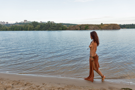 young caucasian beautiful naked Amazon woman walk along river beach at sunset Archivio Fotografico