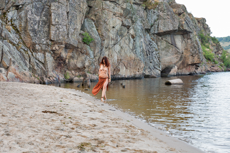 young caucasian beautiful naked Amazon woman walk turned back on the sand river beach in front of rocks