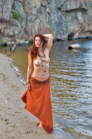 young caucasian beautiful naked Amazon woman with raised hand on the sand river beach in front of rocks Banque d'images