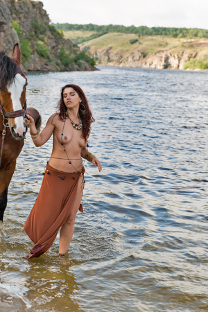 young caucasian beautiful naked Amazon woman on the river shore with red horse