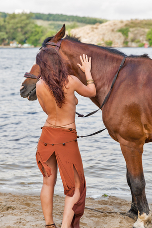 young caucasian beautiful naked Amazon woman on the sand river beach stands turned back with red horse