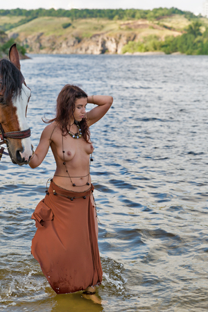 young caucasian beautiful Amazon woman on the river shore with red horse