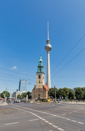 BERLIN, GERMANY - JULY 14, 2018: People walk on Alexanderplatz square with Berlin Tv Tower or Fernsehturm, Park Inn hotel and St. Mary Church or Marienkirche. Berlin is capital and German largest city