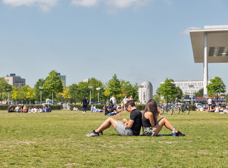 BERLIN, GERMANY - JULY 14,2018: Young people have a rest in front of Bundestag and Paul Lobe buildings on summer meadow. Berlin is the capital and German largest city by both area and population.