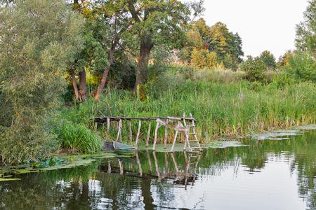 Landscape with boat and fisherman wooden bridge on the River Ros, Central Ukraine. Banco de Imagens