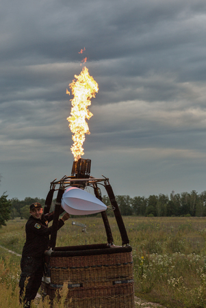 MAKARIV, UKRAINE - JULY 01, 2017: Unrecognized pilot control hot air balloon preparing to flight at early morning. Hot air from a gas burner fills the dome of the balloon. Editorial