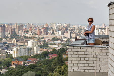 White middle aged tanned woman stands on the roof of a tall building with aerial cityscape in Kiev, Ukraine. Stock Photo