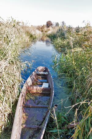 old wooden fisherman boat waterlogged on the autumn riverbank, Ukraine